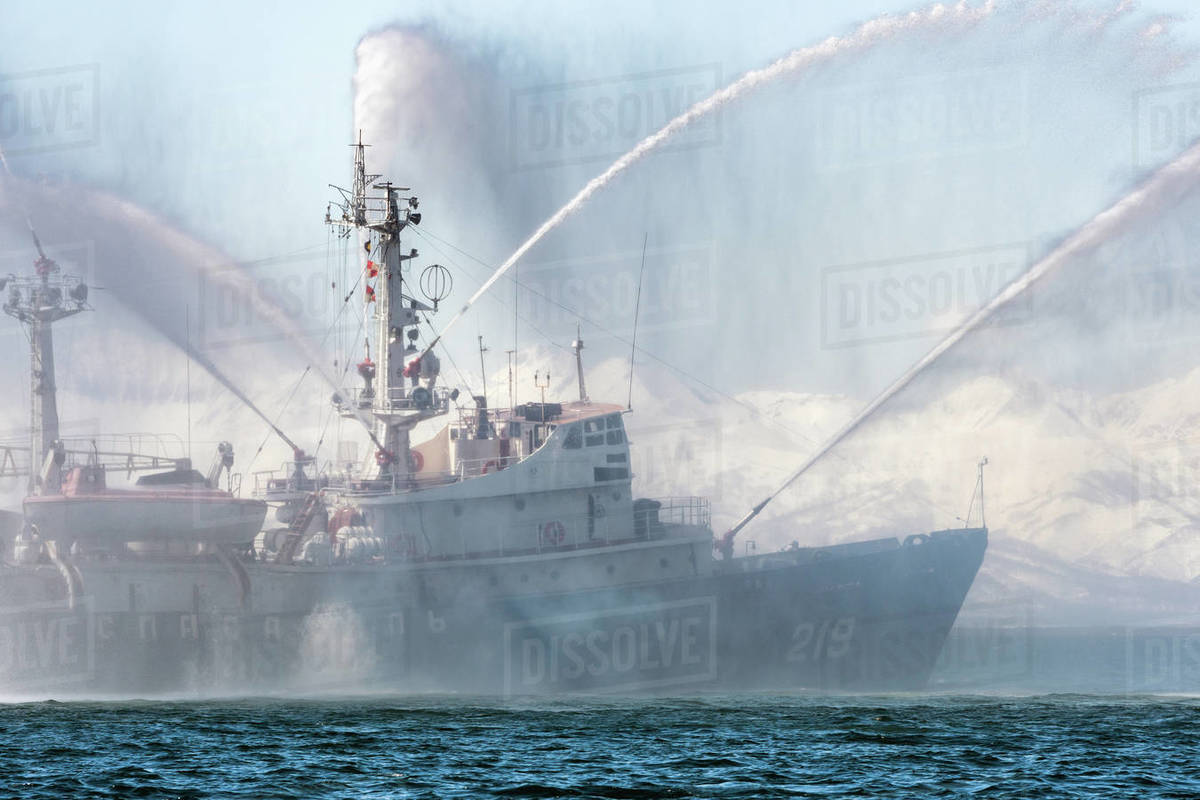 KAMCHATKA, RUSSIA - APR 27, 2019: Firefighting-rescue ship of Pacific Fleet of Russia spraying water on sea for supporting emergency case of fire of warships, passengers ships, gas and oil industry. Royalty-free stock photo