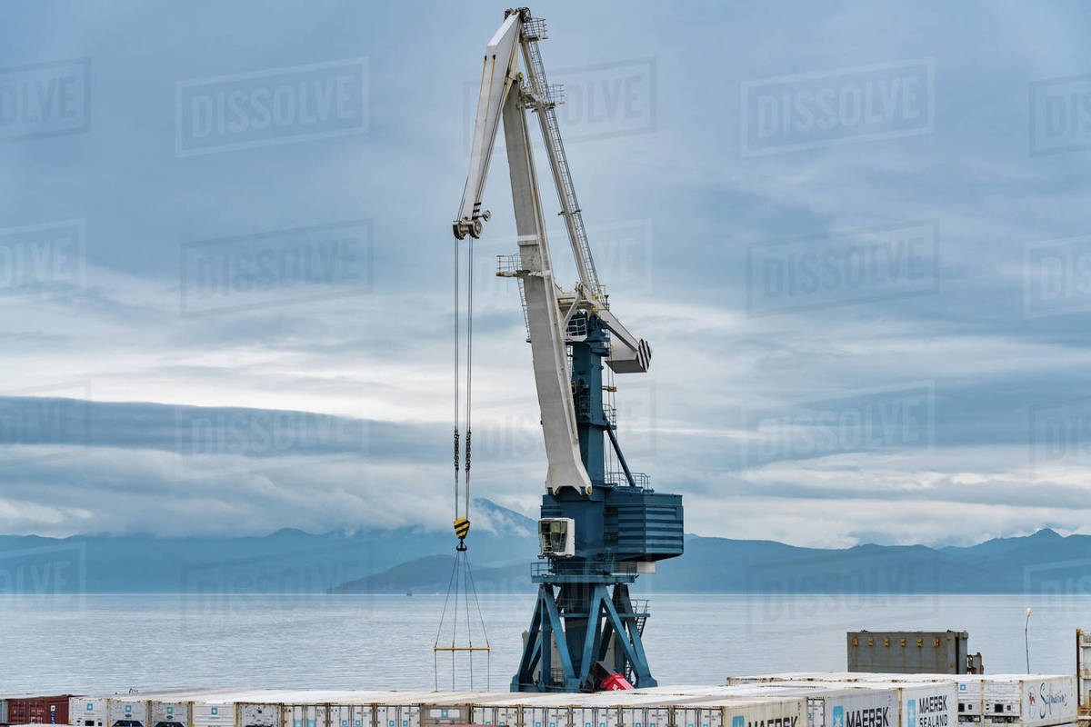 Harbor gantry-crane and many containers for shipping sea storage at terminal in sea port on coast of Pacific Ocean. Petropavlovsk-Kamchatsky City, Kamchatka Peninsula, Russian Far East - Aug 27, 2019. Royalty-free stock photo