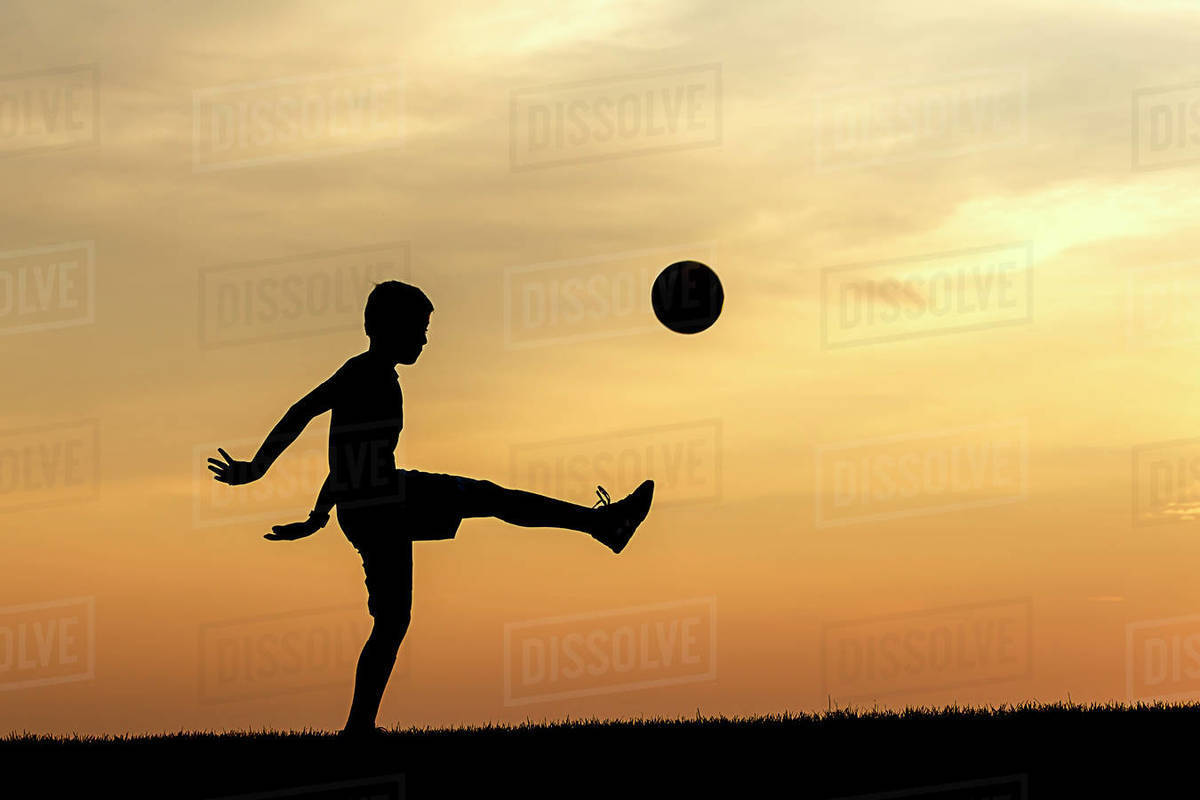 A concept photo of a young athlete practicing soccer at sunset. Royalty-free stock photo