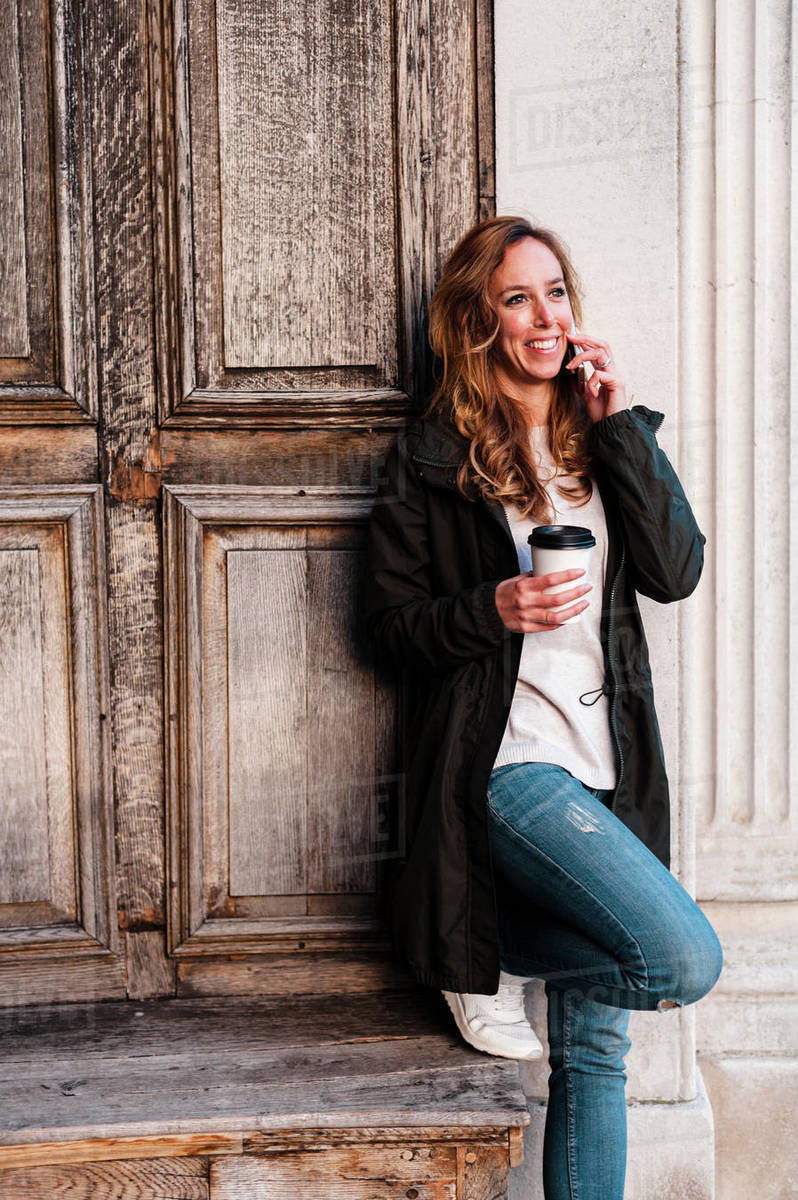 Cheerful adult woman talking by phone holding a cup of coffee wearing casual clothes at urban park on sunny afternoon in London, UK Royalty-free stock photo