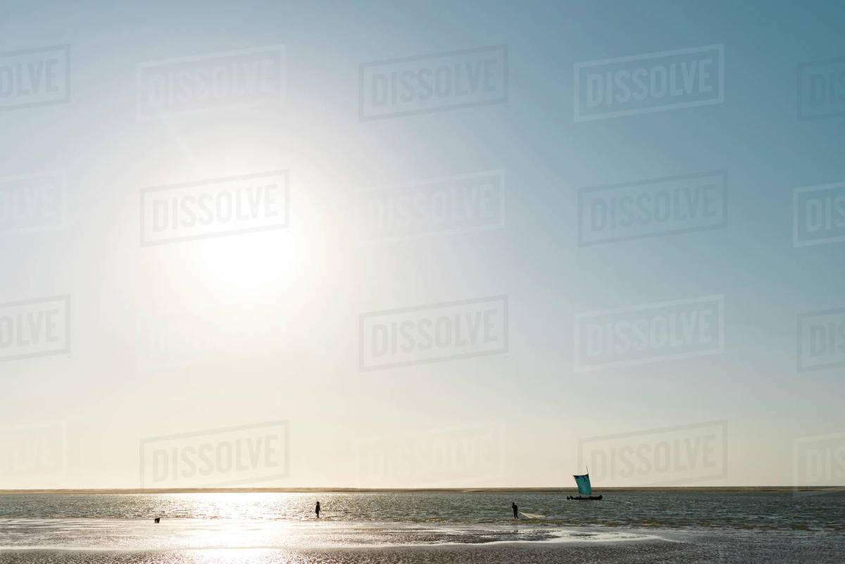 Silhouette of two unrecognizable fishermen with net on the beach at sunset and a boat in Morondava, Madagascar Royalty-free stock photo