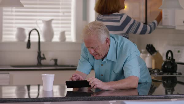 Senior couple in kitchen having morning coffee Royalty-free stock video