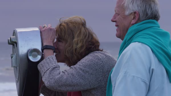 Senior couple at beach looking through viewer Royalty-free stock video