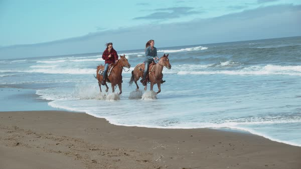 Super slow motion shot of women riding horses at beach, Oregon Royalty-free stock video