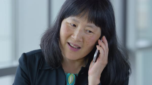 Mature Asian businesswoman using cell phone in office lobby Royalty-free stock video