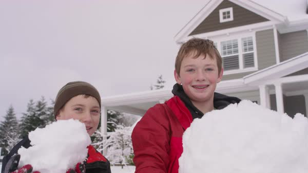 Portrait of two boys holding big snow balls by home in winter Royalty-free stock video