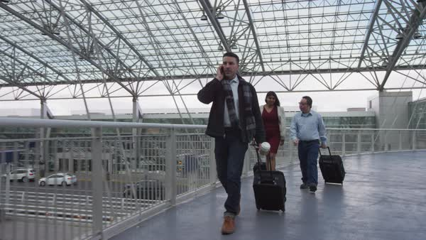 Businessman walking and talking on cell phone at airport Royalty-free stock video