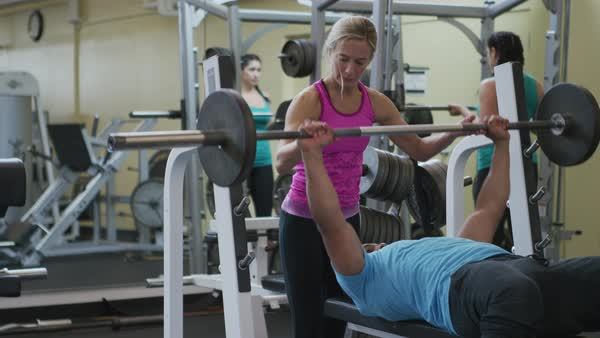 Man and woman at gym lifting weights Royalty-free stock video