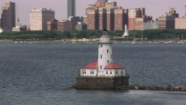 Aerial shot the Chicago Harbor Light lighthouse with downtown Chicago in background.   Royalty-free stock video