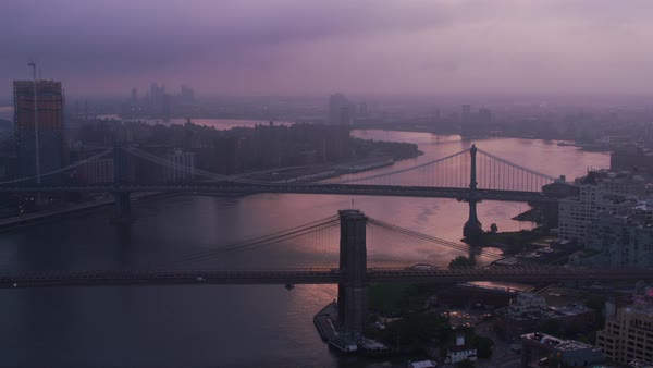 Flying up East River by Brooklyn and Manhattan bridges at sunrise.   Royalty-free stock video