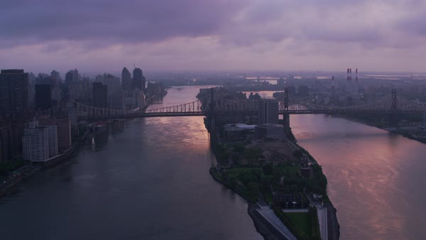 Flying up East River over Roosevelt Island and Queensboro Bridge at sunrise.   Royalty-free stock video