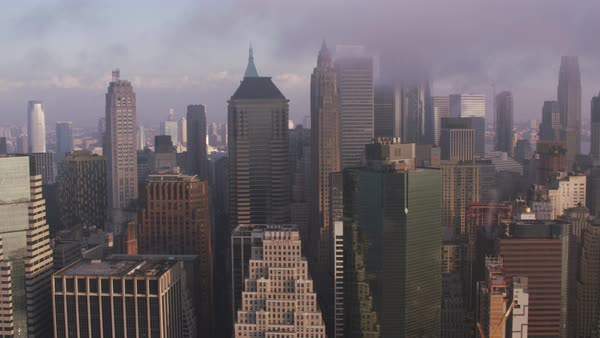 Tracking by lower Manhattan buildings with low clouds and early morning sunshine.    Royalty-free stock video