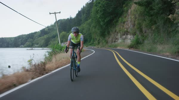 Tracking shot of a female cyclist on country road Royalty-free stock video