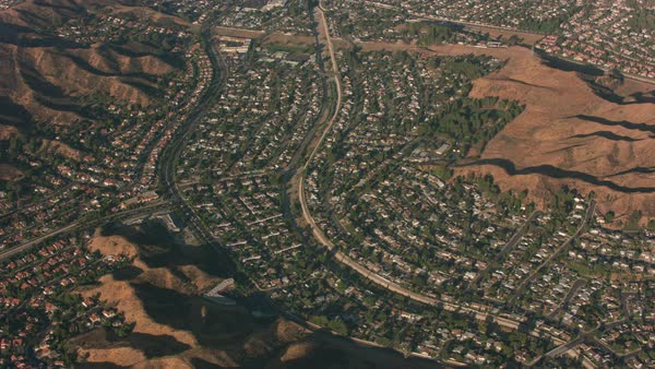 Aerial view of suburban neighborhood between hills in Southern California.   Royalty-free stock video