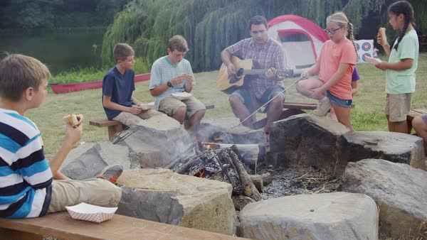 Kids at summer camp by campfire with leader playing guitar Royalty-free stock video