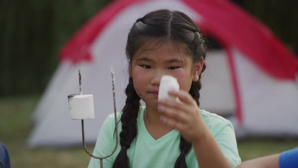 Young girl at summer camp eating a marshmallow Royalty-free stock video