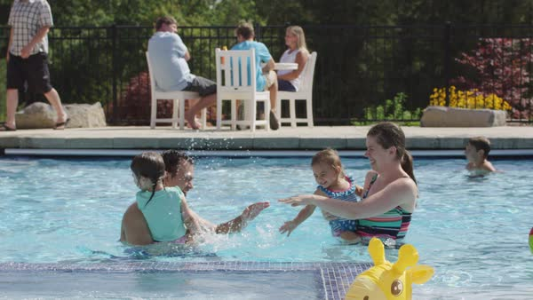 Family playing and splashing in backyard pool Royalty-free stock video