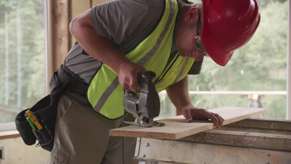 Construction worker cutting wood with jigsaw Royalty-free stock video