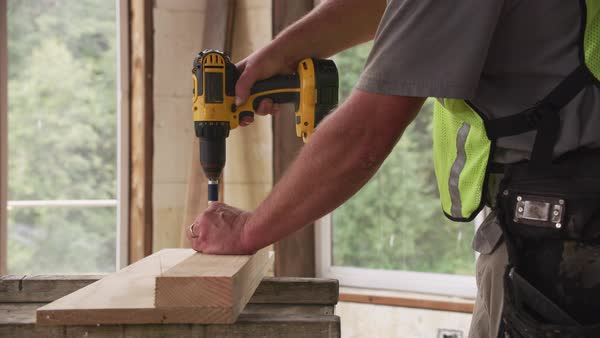 Construction worker using cordless screw gun Royalty-free stock video