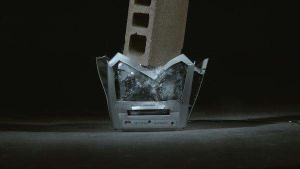 Concrete block is dropped on television in slow motion Royalty-free stock video