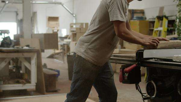 Medium shot of a carpenter sawing a piece of wood Royalty-free stock video