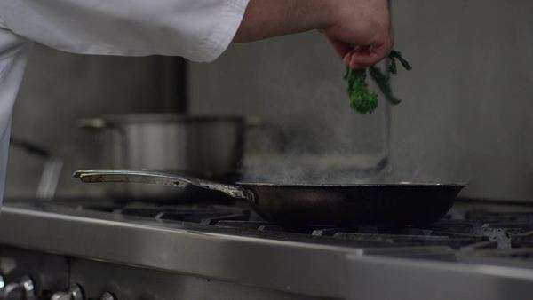 Medium close-up shot of a chef adding vegetables in a pan Royalty-free stock video