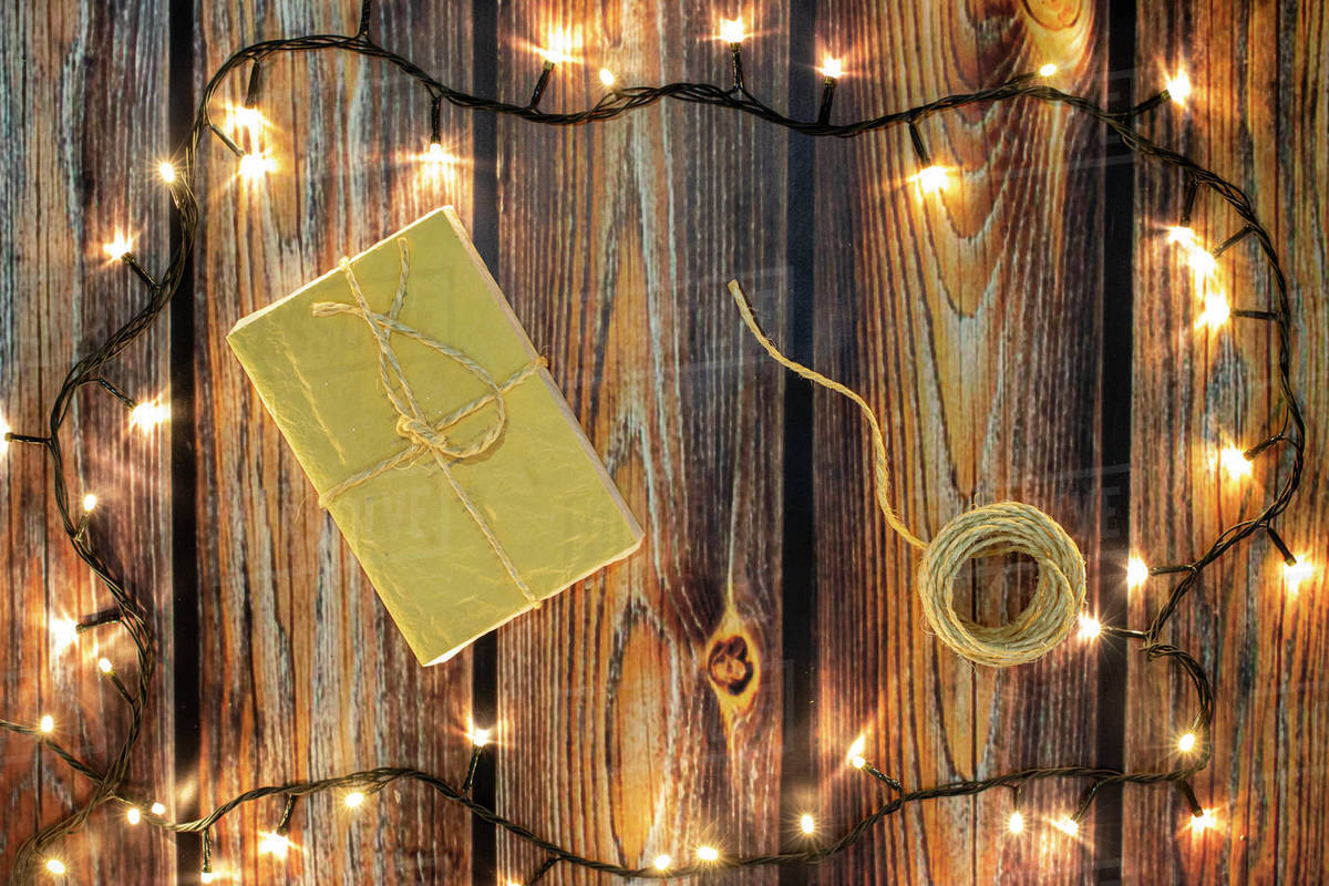 Christmas gifts and lights on wooden floor Royalty-free stock photo