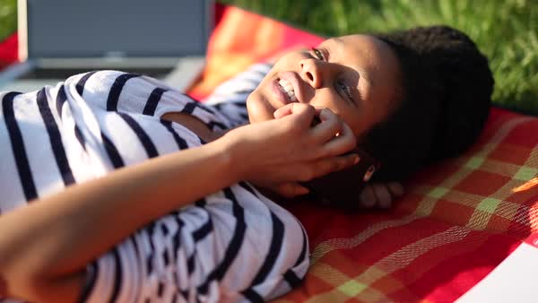 Medium close-up shot of a woman talking on phone while lying on a blanket in a field Royalty-free stock video