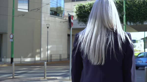 Tracking shot of a woman turning back while walking on a street Royalty-free stock video