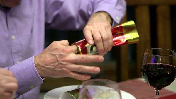 Man opening Christmas cracker at dinner table Royalty-free stock video