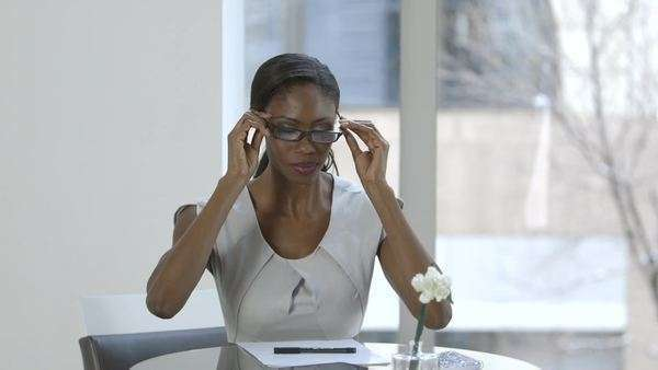 Medium shot of businesswoman putting glasses on and writing Royalty-free stock video
