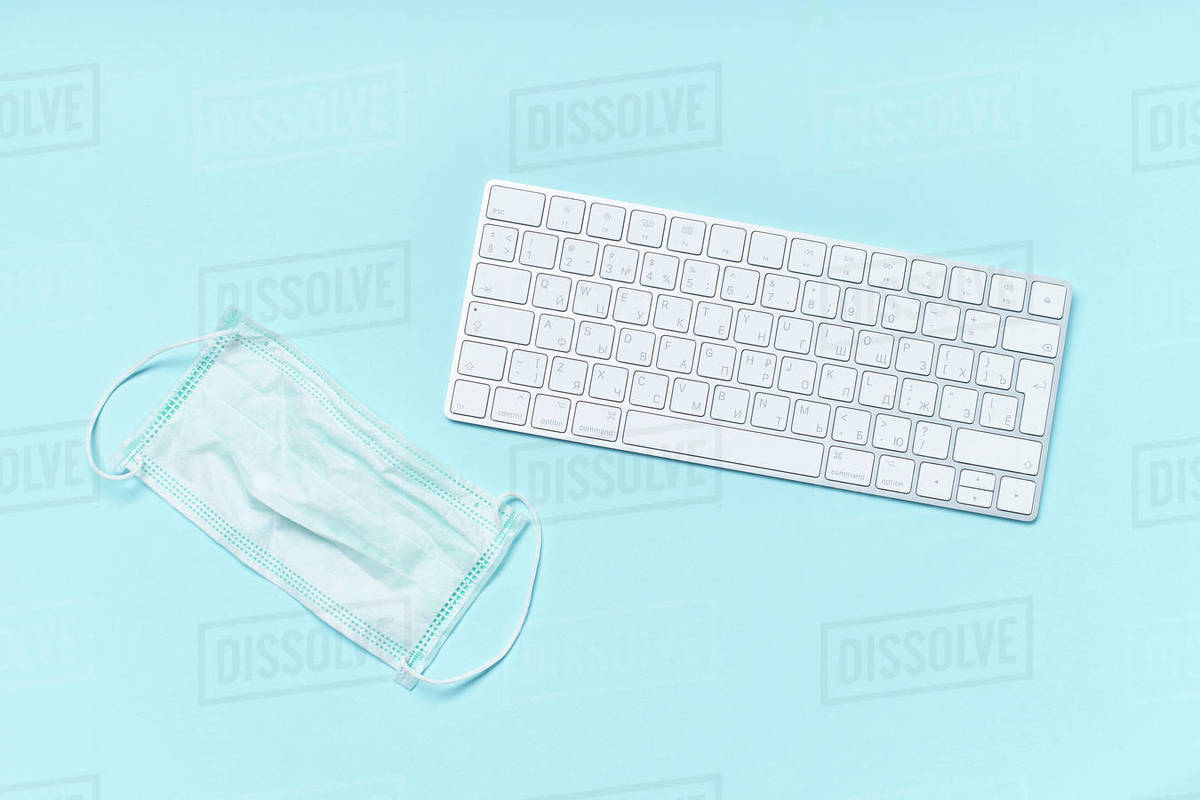 Flatlay with white keyboard and protection mask. Working from home at the time of coronavirus outbreak concept Royalty-free stock photo