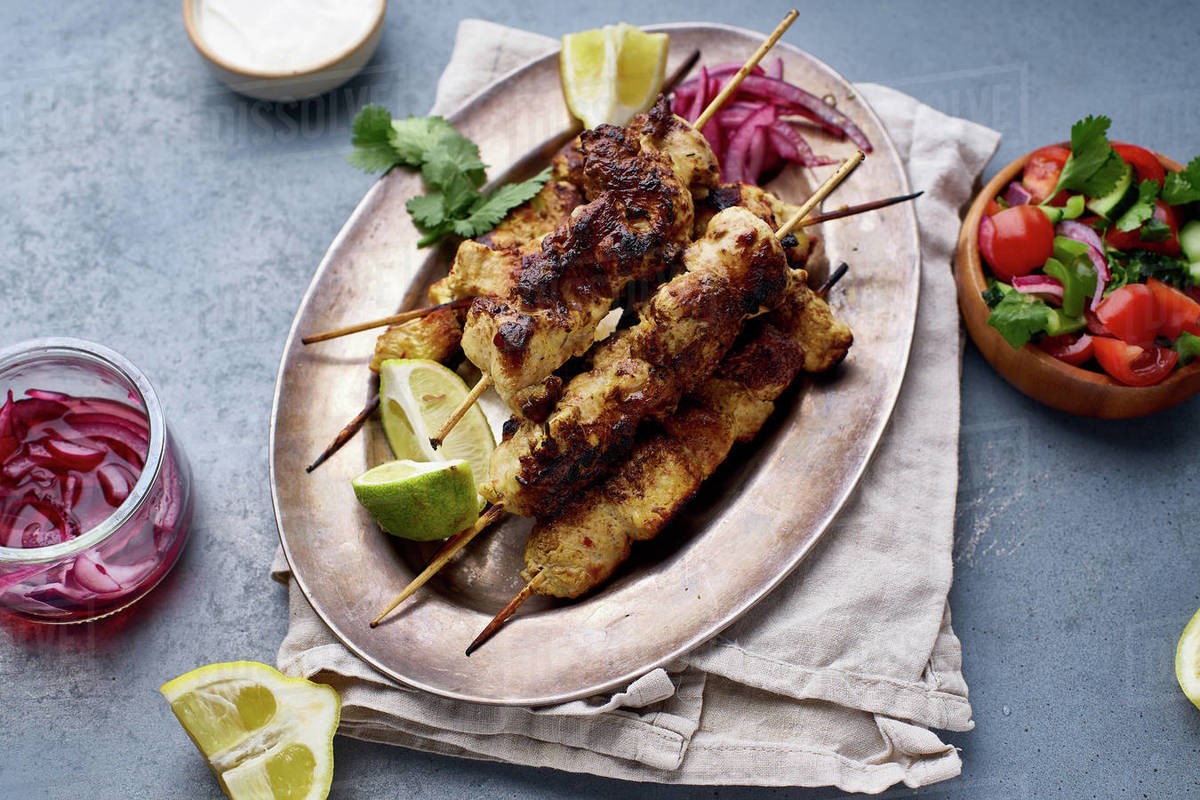 Chicken tikka kebab with marinated onion, fresh salad and yoghurt sauce. Traditional indian cuisine, delicious starter. Creative flatlay Royalty-free stock photo