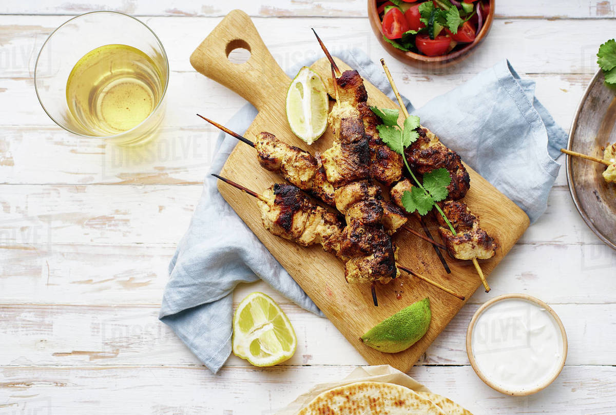Chicken tikka kebab with red onion, coriander and fresh salad. Traditional indian dish made of chicken marinated in yoghurt and spices. Creative flatlay on white wooden background. Royalty-free stock photo