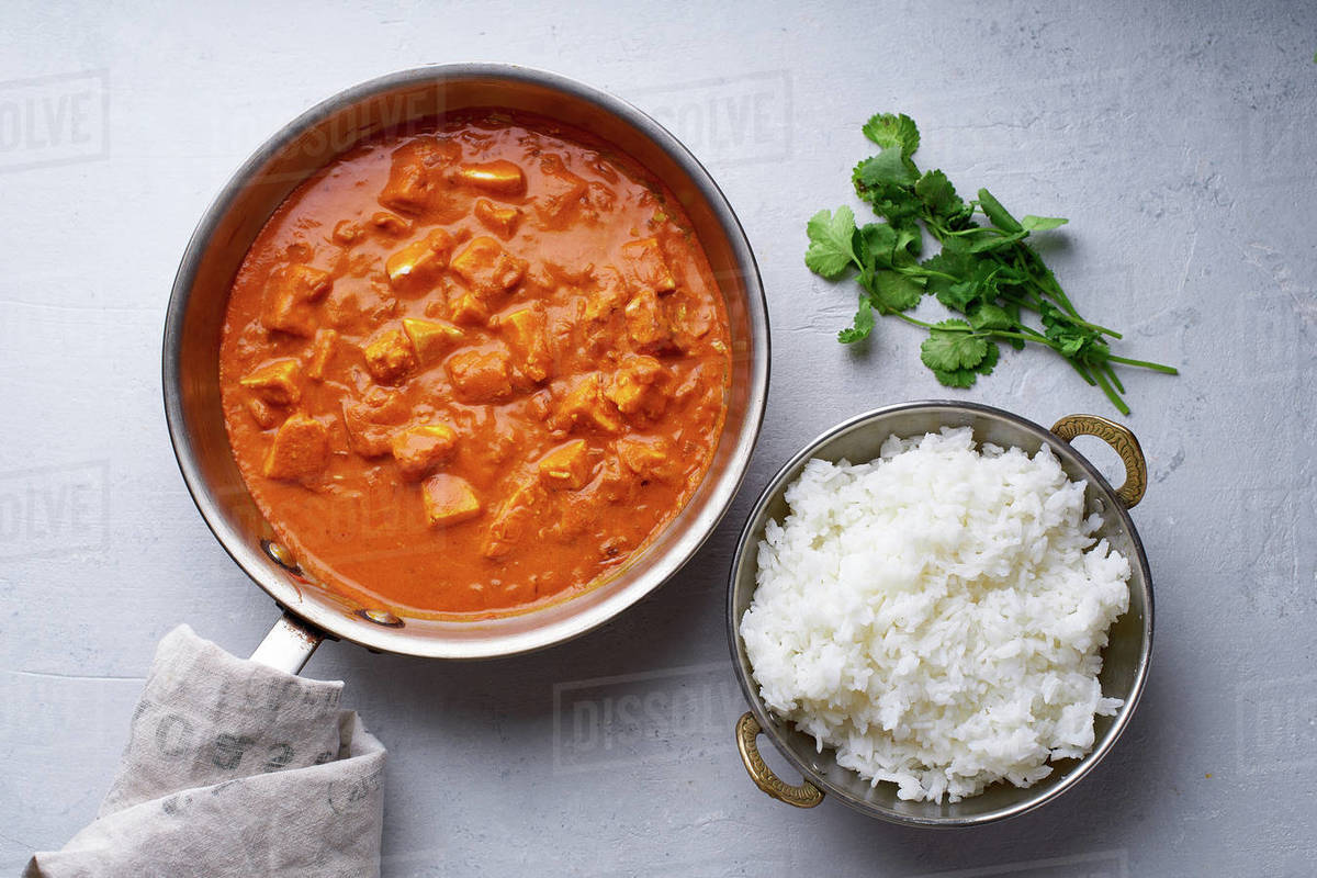 Paneer tikka masala in steel pan with rice on concrete background. Indian cuisine, vegetarian dish made of soft cheese cubes cooked in spicy tomato sauce with cream. Top view. Royalty-free stock photo