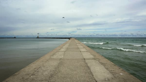 Concrete pier with calm water on one side and waves breaking on the other.  Lighthouse can be seen at the end of the harbor.  Recorded on Lake Michigan at Frankfort, Michigan. Royalty-free stock video