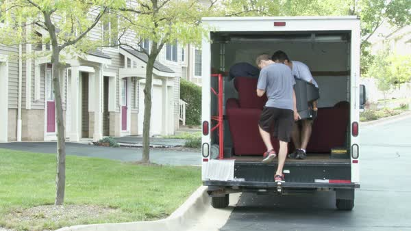 Two guys unload a moving van.  Disolves into timelapse sequence. Royalty-free stock video
