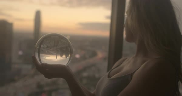 Beautiful young woman gazes into a crystal ball in front of apartment window overlooking south west area of Downtown Los Angeles at sunset. Close up with focus on ball, recorded in slow motion. Royalty-free stock video