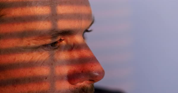 Big close up on a man's brown eyes looking to side, his face illuminated by warm orange light coming through window blinds Royalty-free stock video