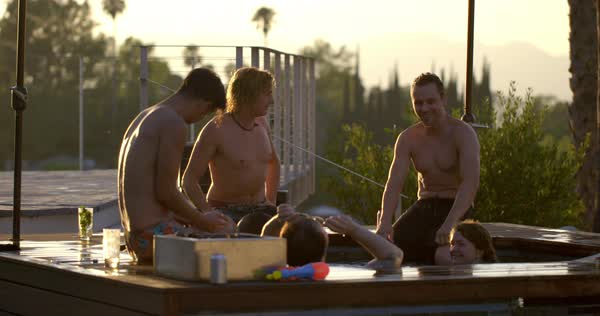 Friends sit around a hot tub with fire pit in golden afternoon sunlight, enjoying drinks and talking at fabulous resort location with umbrellas and palm trees. Slow motion  Royalty-free stock video