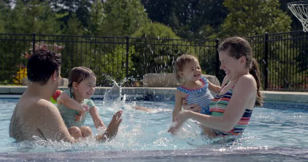 Mom and dad stand holding infant daughters in swimming pool while they all splash water at each other on sunny summer day Royalty-free stock video