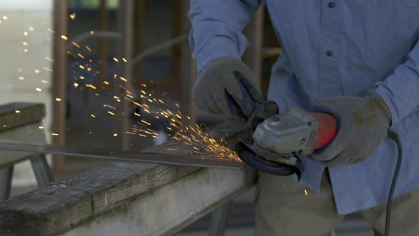 Workman using angle grinder to clean up a piece of metal, creating a shower of sparks inside a house under construction Royalty-free stock video