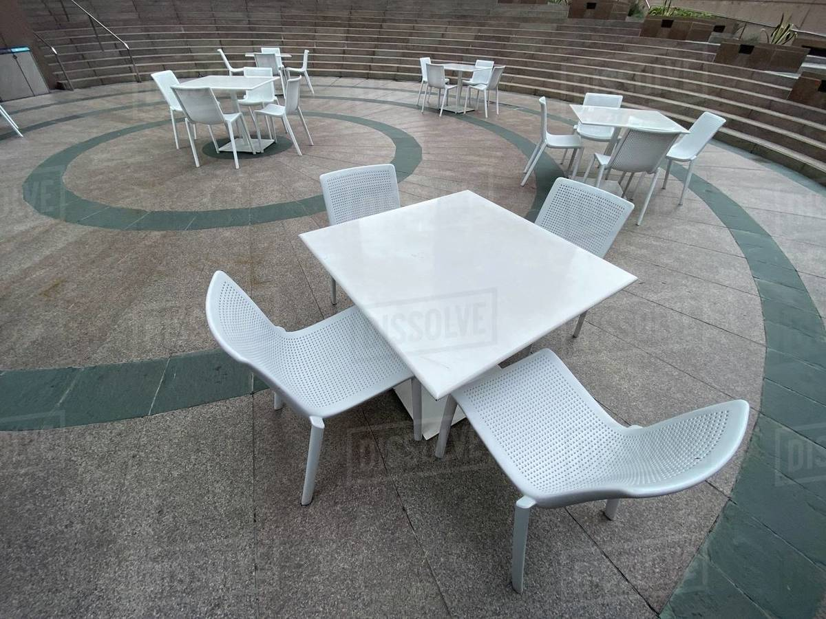 """LOS ANGELES, CA, MAR 2020: wide angle view of empty white-coated steel chairs and tables in Downtown during coronavirus, Covid-19 """"stay at home"""" order Royalty-free stock photo"""