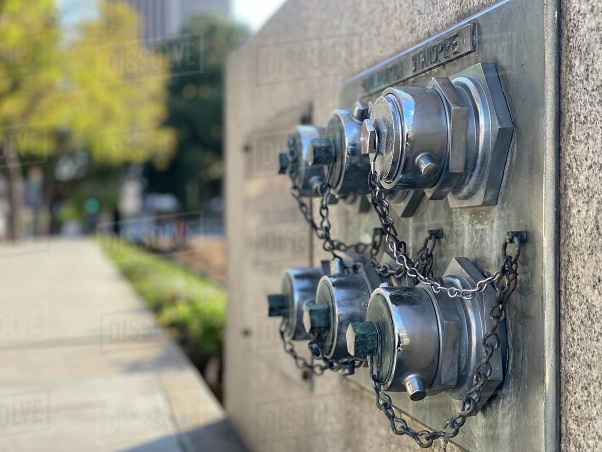 Detail of shiny, steel standpipes outside a building in Downtown Los Angeles. Soft focus cityscape in background Royalty-free stock photo