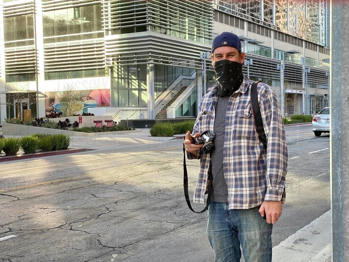Photographer wearing bandana to cover face poses between taking pictures on streets in Downtown Los Angeles during coronavirus, Covid-19 pandemic. Identifying logos and signage removed Royalty-free stock photo