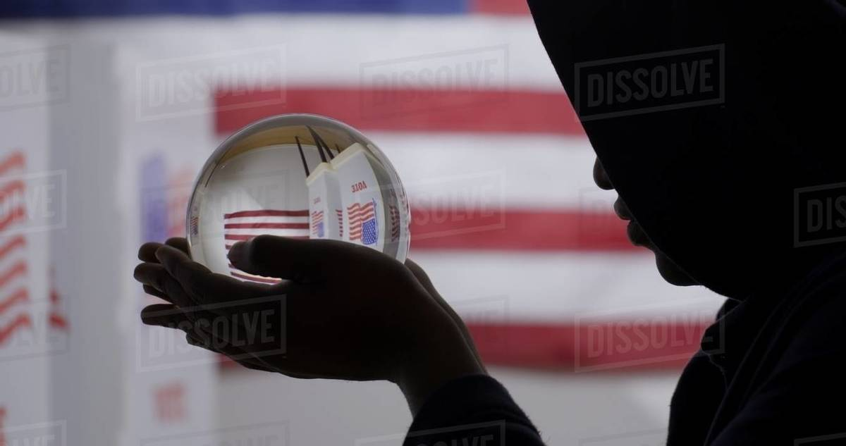 CU silhouetted African American man in a hoodie obscuring his face, looks at crystal ball showing voting booths in front of US flag Royalty-free stock photo