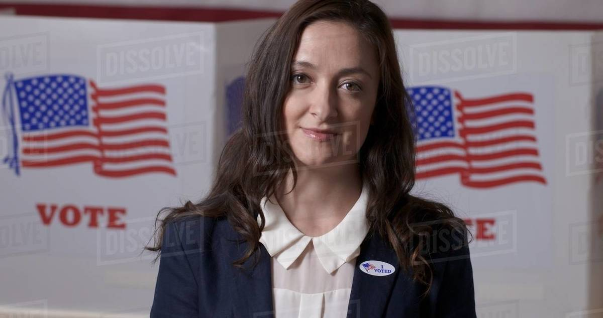 """Close up Caucasian businesswoman in smart jacket wearing """"I Voted"""" sticker  and posing, proudly in front of polling booths with US flag Royalty-free stock photo"""