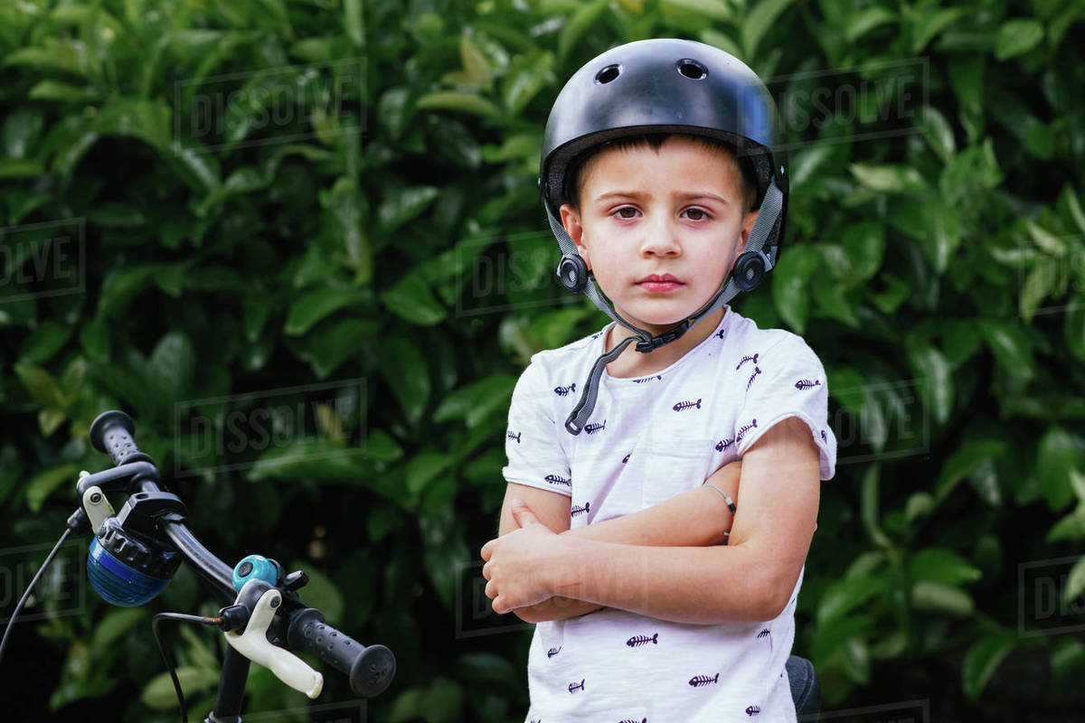 portrait of a 4 year old boy, sitting on his bike on a green background Royalty-free stock photo