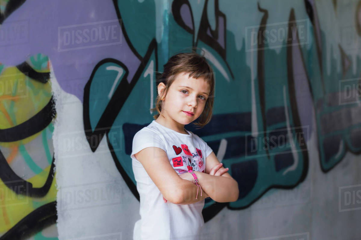 Portrait of a 6 year old blonde stone girl on a spray painted wall. Concept of girl power Royalty-free stock photo
