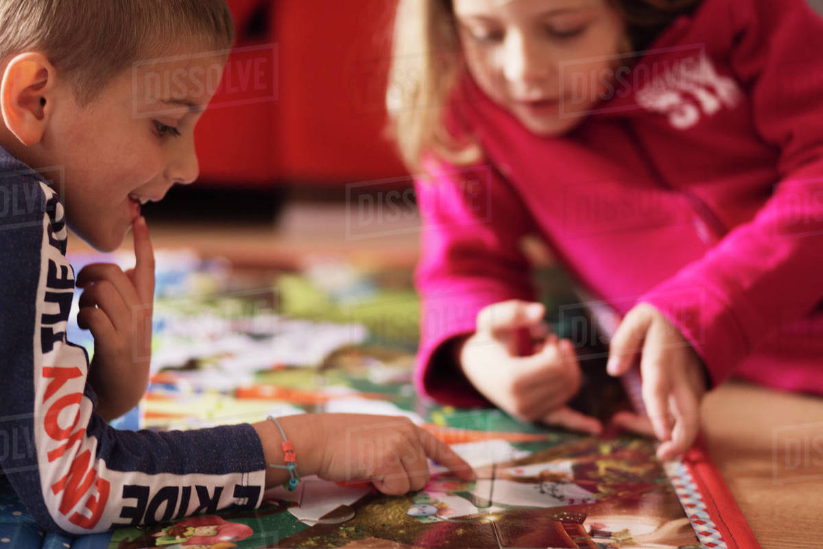 middle plane of two brothers doing a puzzle at home. Concept of cooperation Royalty-free stock photo